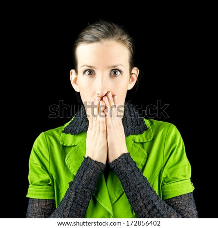 Woman reacting in shock or amazement holding her hands to her mouth as she stares at the camera with a wide-eyed expression - stock photo