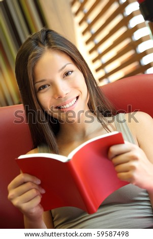 Woman reading a book at home. Young beautiful Caucasian / Asian female model - stock photo