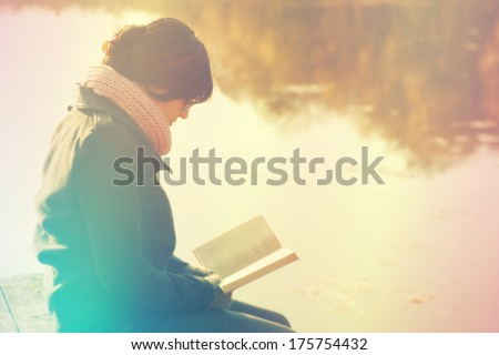Woman reading a book at the lake - stock photo