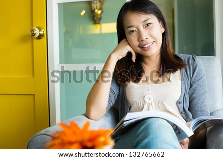 Woman reading a book on sofa in cafe restaurant - stock photo
