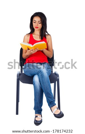 Woman reading a book sitting on chair - isolated on white. - stock photo