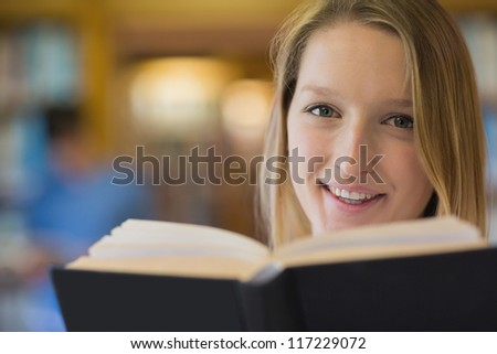 Woman reading a book while smiling - stock photo