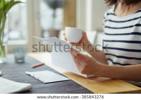 Woman reading a document at the dining table as she enjoys a morning cup of coffee, close up view of her hands - stock photo