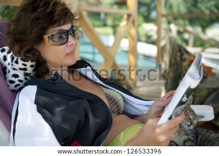 Woman reading a magazine on holiday with a kitten