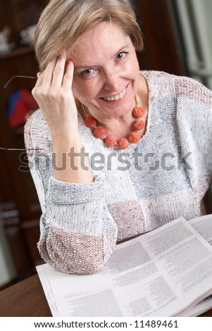 Woman reading a newspaper, portrait - stock photo