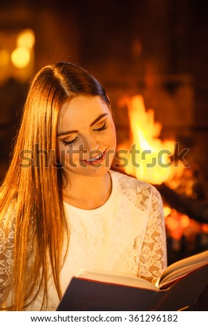 Woman reading book at fireplace. Young girl heating warming up and relaxing. Winter at home. - stock photo