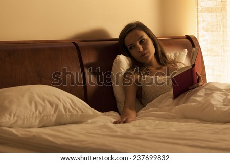 Woman reading book in bed and waiting for boyfriend - stock photo