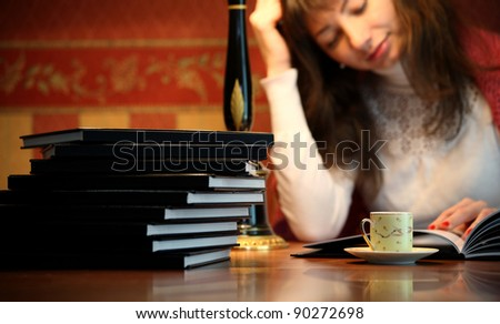 Woman reading book in office desk cup of coffee on (focus on books and cup) - stock photo