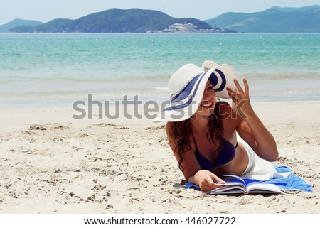 Woman reading book near the ocean
