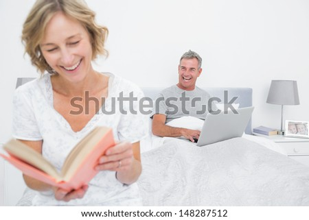 Woman reading book while husband is using laptop in bedroom at home - stock photo