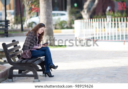 woman reading digital book at the park - stock photo