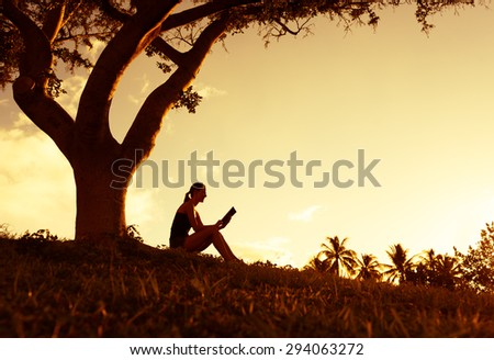 Woman reading in the park. - stock photo