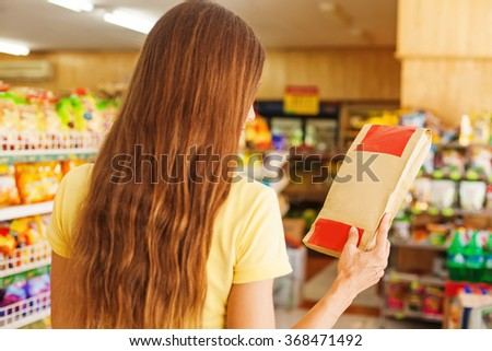 woman reading ingredients from the blank package in shop - stock photo
