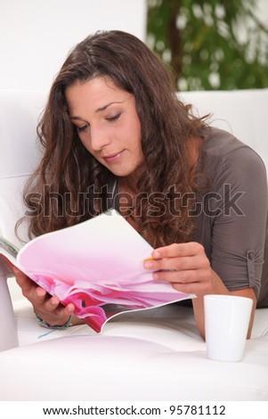 Woman reading magazine - stock photo