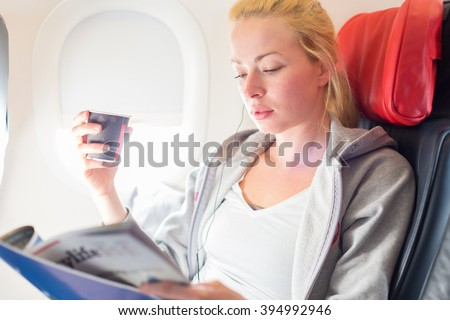 Woman reading magazine and drinking coffeeon airplane. Female traveler reading seated in passanger cabin. Sun shining trough airplane window. - stock photo