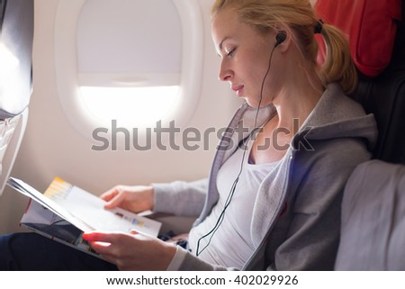 Woman reading magazine and listening to music on airplane. Female traveler reading seated in passanger cabin. Sun shining trough airplane window. - stock photo