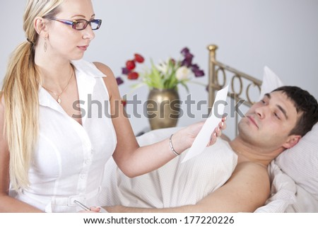Woman reading medical report in front of sick man on the bed - stock photo