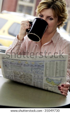 woman reading newspaper - stock photo