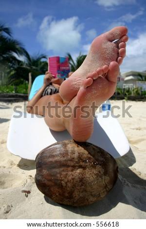 Woman reading on tropical beach - stock photo