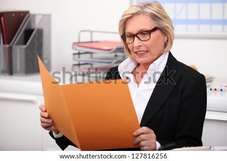 Woman reading report - stock photo