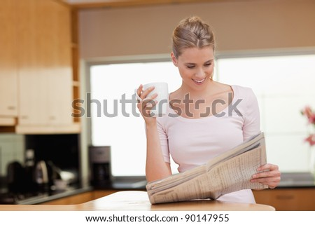 Woman reading the news while having tea in her kitchen - stock photo