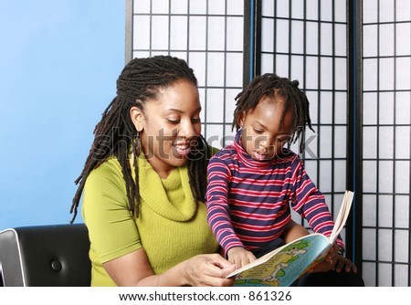 Woman reading to her little boy - stock photo