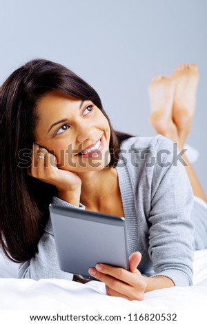 woman reading with modern digital tablet device while lying on bed isolated on grey background - stock photo