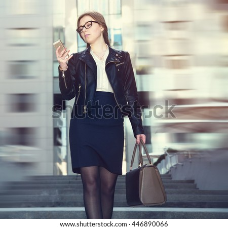 Woman reads a message on your phone. Woman wearing glasses and hold smart phone.  - stock photo