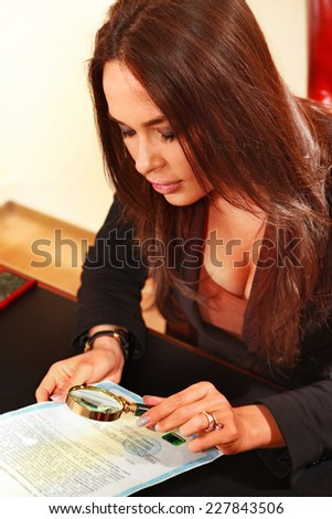 woman reads the document by means of a magnifying glass - stock photo