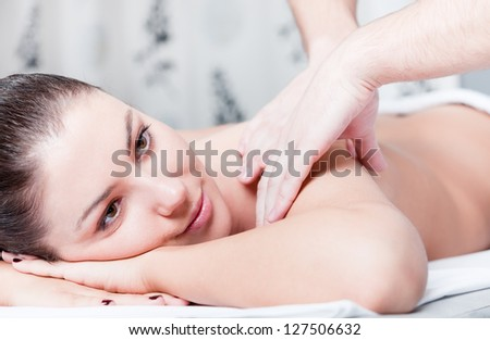 Woman receives body massage at spa