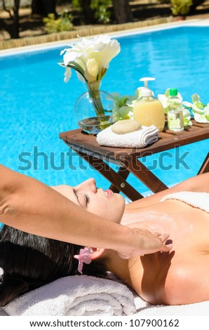 Woman receives massage in spa club near pool in summer.