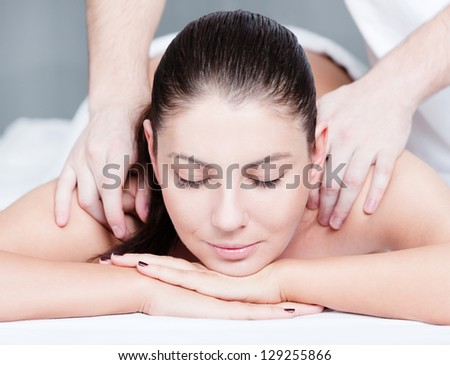 Woman receives shoulders massage at spa - stock photo