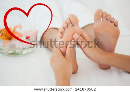 Woman receiving a foot massage against heart - stock photo