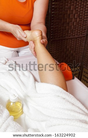 Woman receiving a leg and foot massage and lymphatic drainage while lying on a towel in a awarded health massage center,  series of various techniques