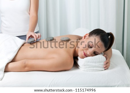 Woman receiving a stone massage in spa.
