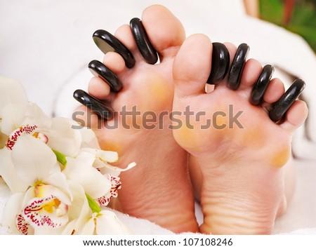 Woman receiving hot stone massage on feet. - stock photo