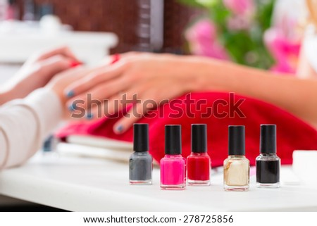 Woman receiving manicure in beauty parlor, her nails being polished - stock photo