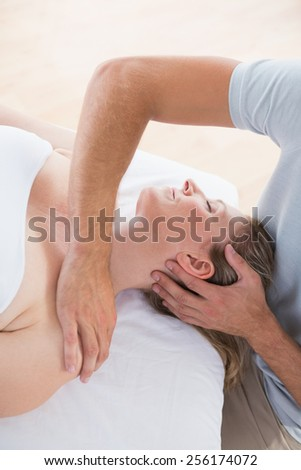 Woman receiving neck massage in spa centre
