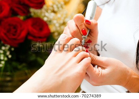 Woman receiving pedicure in a Day Spa; lots of flowers in the background - stock photo