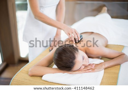 Woman receiving stone massage from female masseur at health spa - stock photo