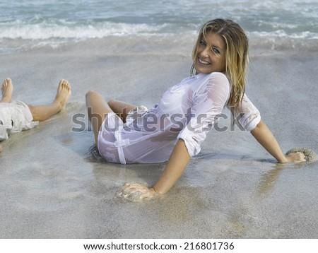 Woman reclining on the beach - stock photo