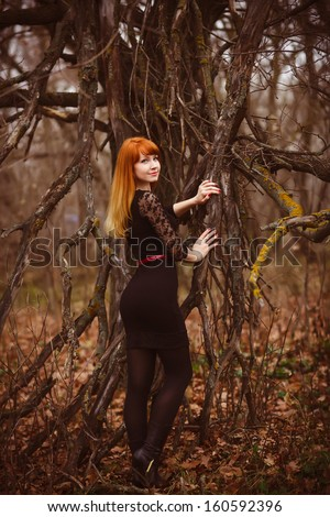 woman red-haired model girl in black dress dry autumn dark forest, dry branches on street