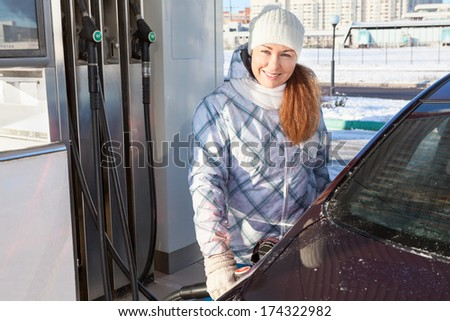 Woman refueling car with petroleum at winter season - stock photo