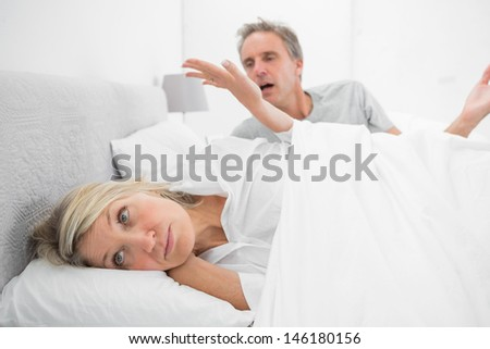 Woman refusing to listen to partner during a fight in bed at home in bedroom - stock photo