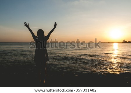woman relax on the beach when sunset time after working hard vintage retro silhouette