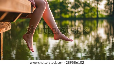 Woman relaxes by the lake sitting on the edge of a wooden jetty , swing one's feet near the water surface. Sunny joyful summer day or evening concept.