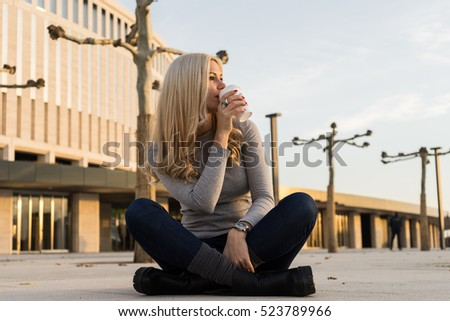 Woman relaxing after a long working day sitting in yoga lotus positions and drinking coffee from white cup on the street.Sunset time,modern urban city background.Relaxation and healthy concept