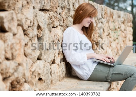 Woman relaxing against a stone wall on a ledge sitting typing on her laptop computer balanced on her lap - stock photo