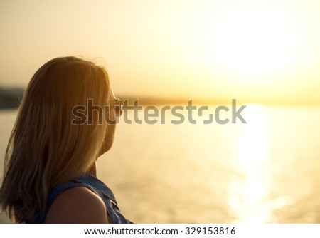 Woman relaxing against sunset. Place for text. - stock photo