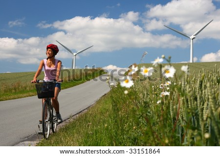 Woman relaxing and enjoying the sun on a bike trip in the countryside of Jutland, Denmark. Wind turbines in the background. - stock photo